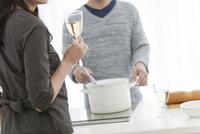 調理をする夫と妻の手元
