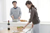 調理をする夫と料理を運ぶ妻