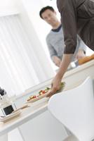 調理をする夫と料理を運ぶ妻の手元