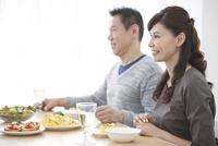 食卓に座る笑顔の中高年夫婦