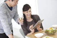 食卓でスマートフォンを操作する妻と夫