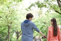 自転車を押すカップルの後姿 07800054756| 写真素材・ストックフォト・画像・イラスト素材|アマナイメージズ