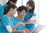 ノートパソコンを見て話す男女5人