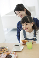 お菓子を食べる娘と母親
