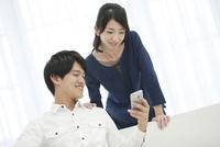スマートフォンを見て話す夫婦