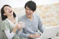 ノートパソコンを見て笑う夫婦 07800055305| 写真素材・ストックフォト・画像・イラスト素材|アマナイメージズ