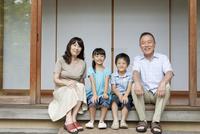 縁側に座る祖父母と孫 07800055390| 写真素材・ストックフォト・画像・イラスト素材|アマナイメージズ