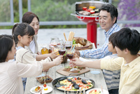 テラスで食事する3世代家族
