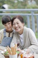 テラスで食事する孫と祖母 07800055608| 写真素材・ストックフォト・画像・イラスト素材|アマナイメージズ