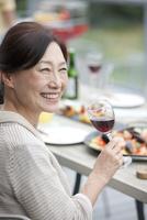 テラスで食事する中年女性