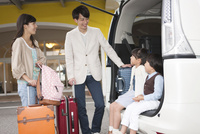 車から荷物をおろす4人家族