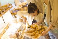 パンをトレイにのせる女の子 07800055755| 写真素材・ストックフォト・画像・イラスト素材|アマナイメージズ