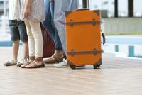 旅行かばんと4人家族の足元