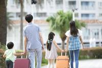 スーツケースを引いて歩く4人家族