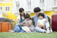 芝生でタブレットPCを見る4人家族