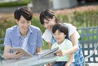 タブレットPCを見る3人家族