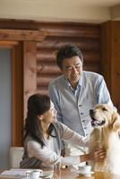 犬をあやす中高年夫婦 07800056013| 写真素材・ストックフォト・画像・イラスト素材|アマナイメージズ