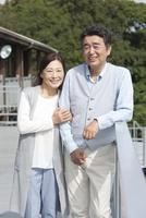 テラスに立つ笑顔の中高年夫婦