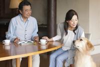 犬をあやす中高年夫婦 07800056041| 写真素材・ストックフォト・画像・イラスト素材|アマナイメージズ