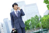 スマートフォンで電話をするビジネスマン 07800056113| 写真素材・ストックフォト・画像・イラスト素材|アマナイメージズ