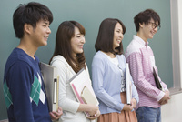 黒板の前に立つ学生たち