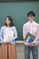 黒板の前に立つ学生2人