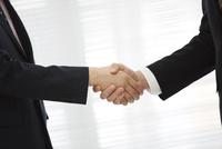 握手をするビジネスマンの手元