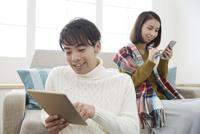 タブレットPCとスマートフォンを操作する男女