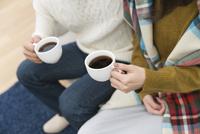 コーヒーカップを持つ男女の手元
