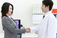 握手をする研究員とビジネスウーマン