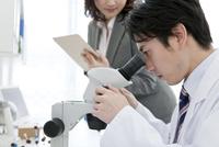 顕微鏡を覗く研究員とビジネスウーマン