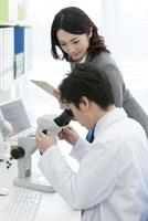 顕微鏡を覗く研究員とビジネスウーマン 07800056520| 写真素材・ストックフォト・画像・イラスト素材|アマナイメージズ