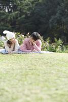 公園の芝生に寝そべるカップル
