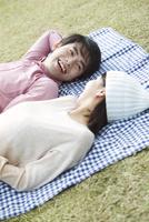 公園の芝生に寝そべるカップル 07800056603| 写真素材・ストックフォト・画像・イラスト素材|アマナイメージズ
