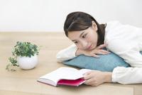 床に寝そべり本を読む女性