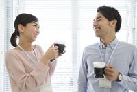 コーヒーカップを持つビジネス男女