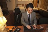 ホテルの部屋でパソコンを操作する男性