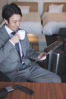 ホテルの部屋でタブレットPCを見るビジネスマン 07800056973| 写真素材・ストックフォト・画像・イラスト素材|アマナイメージズ