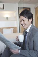 ホテルの部屋で新聞を読むビジネスマン 07800056980| 写真素材・ストックフォト・画像・イラスト素材|アマナイメージズ