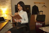 ホテルの部屋で手帳を見る女性