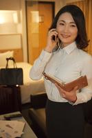 ホテルの部屋で電話をする女性 07800056988| 写真素材・ストックフォト・画像・イラスト素材|アマナイメージズ