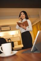 ホテルの部屋で電話をする女性 07800056989| 写真素材・ストックフォト・画像・イラスト素材|アマナイメージズ