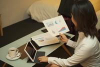 ホテルの部屋で資料を見る女性 07800057003| 写真素材・ストックフォト・画像・イラスト素材|アマナイメージズ