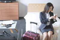 ベッドでスマートフォンを見るビジネスウーマン 07800057009| 写真素材・ストックフォト・画像・イラスト素材|アマナイメージズ