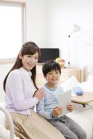 タブレットPCを持つ男の子と母親