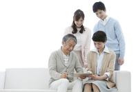 タブレットPCを見る家族4人