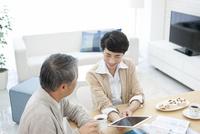 タブレットPCを見て話す中高年夫婦