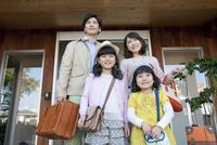 玄関の前に立つ家族4人