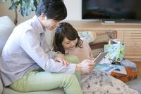 タブレットPCを見ているカップル 07800057508| 写真素材・ストックフォト・画像・イラスト素材|アマナイメージズ