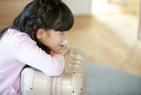 スーツケースにもたれる女の子